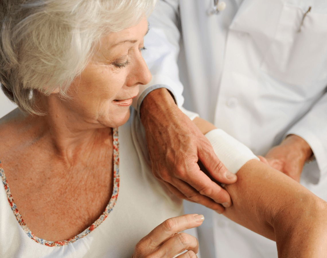 Woman receiving help getting her wound covered on her arm