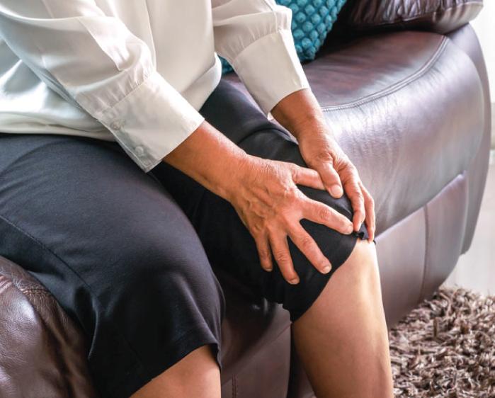 Woman grabbing her sore knee
